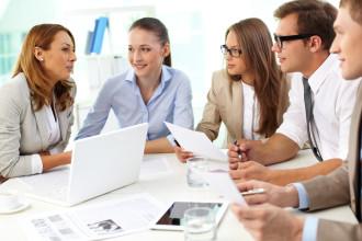 Fünf junge Menschen sitzen am Bürotisch