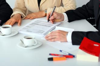 Steuerberater im Gespräch mit Mandantenpaar am Schreibtisch. Auf dem Schreibtisch befinden sich Unterlagen zur Steuererklärung und ein Gesetzestext.