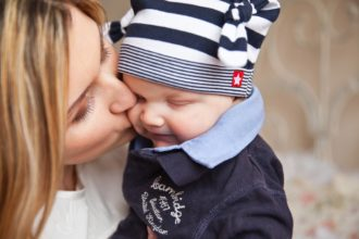 Mutter küsst Baby auf die Wange